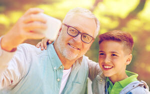 man-nearing-retirement-taking-selfie-with-his-grandson-1